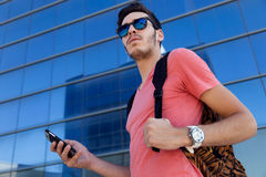 Handsome young man using his mobile phone in the street. Royalty Free Stock Images