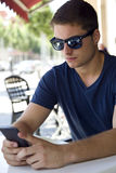 Handsome young man using his mobile phone in the street. Stock Image