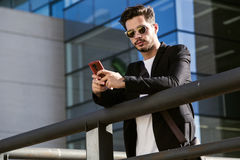 Handsome young man using his mobile phone in the street. Portrait of handsome young man using his mobile phone in the street Royalty Free Stock Photo