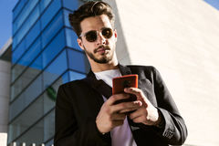 Handsome young man using his mobile phone in the street. Portrait of handsome young man using his mobile phone in the street Royalty Free Stock Images