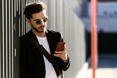Handsome young man using his mobile phone in the street. Portrait of handsome young man using his mobile phone in the street Stock Image