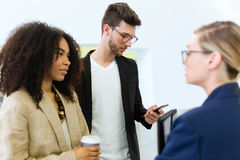 Handsome young man using his mobile phone while two partners talking in a hallway of the company. Royalty Free Stock Photos