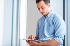Handsome young man using his tablet computer Royalty Free Stock Images