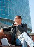 Handsome young man using a laptop. Portrait of a handsome young man with a laptop sitting in front of a building Stock Photography