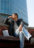 Handsome young man using a laptop. Portrait of a handsome young man with a laptop sitting in front of a building Stock Images