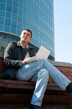 Handsome young man using a laptop. Portrait of a handsome young man with a laptop sitting in front of a building Royalty Free Stock Image