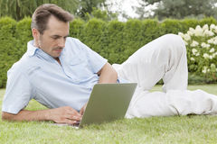 Handsome young man using laptop in park Royalty Free Stock Photography