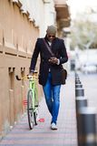 Handsome young man using mobile phone and fixed gear bicycle in the street. Portrait of handsome young man using mobile phone and fixed gear bicycle in the Stock Photo