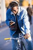 Handsome young man using mobile phone and fixed gear bicycle in the street. Portrait of handsome young man using mobile phone and fixed gear bicycle in the Stock Photos