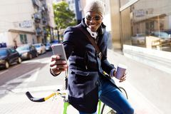 Handsome young man using mobile phone and fixed gear bicycle in the street. Portrait of handsome young man using mobile phone and fixed gear bicycle in the Royalty Free Stock Images