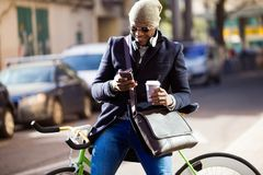 Handsome young man using mobile phone and fixed gear bicycle in the street. Portrait of handsome young man using mobile phone and fixed gear bicycle in the Royalty Free Stock Photos