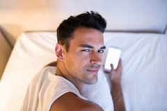 Handsome young man using a mobile phone and messaging in the whi. Te bed. Look at the camera Royalty Free Stock Photos