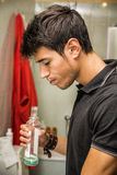 Handsome young man using mouthwash, in bathroom Royalty Free Stock Images