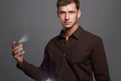 Handsome young man using perfume.perfume bottle and spraying fragrance. In hand of boy Stock Photography