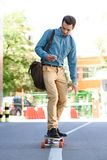 Handsome young man using smartphone and riding longboard. On street stock photography