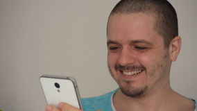 Handsome young man using smartphone and smiling stock video