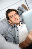 Handsome young man using tablet at home Stock Image