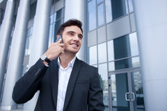 Handsome young man is using telephone for Royalty Free Stock Image