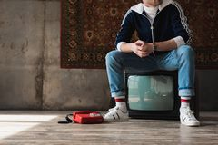 Handsome young man in vintage clothes sitting on retro tv set near red wired telephone in front of rug hanging. On wall stock images