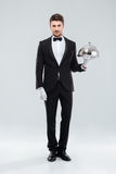 Handsome young man waiter holding tray and lid Royalty Free Stock Image