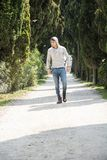 Handsome young man walking along rural road Royalty Free Stock Photo