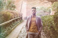 Handsome young man walking along rural road Royalty Free Stock Photography