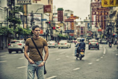 Handsome young man walking in Bangkok, Thailand. Muscular young handsome man walking on busy sunny street in Bangkok, Thailand Stock Image