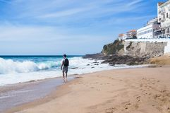 Handsome young man walking barefoot on a deserted beach. On background of blue sky and the stormy ocean Stock Image