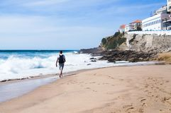 Handsome young man walking barefoot on a deserted beach royalty free stock photos