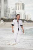 Handsome young man walking on the beach Stock Image