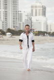 Handsome young man walking on the beach Royalty Free Stock Image