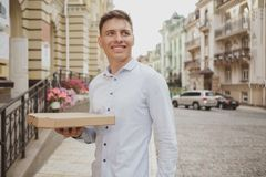 Handsome young man walking on city street with pizza box. Cheerful young man smiling, looking away, carrying tasty pizza from takeaway restaurant. Happy man royalty free stock photo