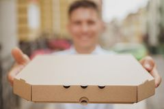 Handsome young man walking on city street with pizza box. Happy man smiling, holding out pizza box to the camera, copy space. Cheerful man carrying delicious royalty free stock photos