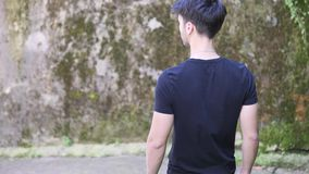 Handsome young man walking down narrow town street stock video