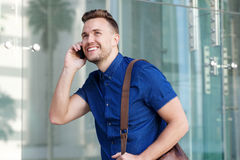 Handsome young man walking with mobile cellphone and bag Stock Image