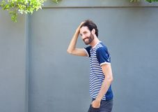 Handsome young man walking outdoors with hand in hair Royalty Free Stock Image