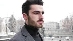Young man in snowy city in Italy. Handsome young man walking outside during winter, in snowy Turin, Italy, in urban setting stock video footage