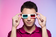 Handsome young man watching movie. Attractive male adjusting anaglyph glasses stock photos