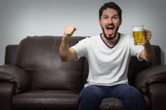 Handsome young man watching TV and cheering while sitting on the Stock Image