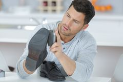 Handsome young man waxing shoes at home. Handsome young man waxing his shoes at home Stock Photos