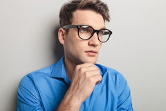 Handsome young man wearing black glasses. Portrait of a handsome young man wearing black glasses, looking away from the camera Royalty Free Stock Photo
