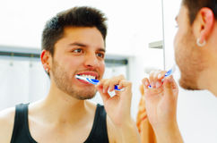 Handsome young man wearing black singlet top looking in mirror smiling while brushing teeth.  Royalty Free Stock Photos