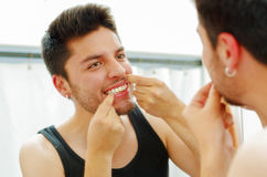 Handsome young man wearing black singlet top looking in mirror, using dental floss during morning routine concept Royalty Free Stock Images
