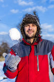 Handsome young man wearing cap and gloves playing with a snowbal Royalty Free Stock Photography