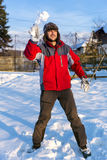 Handsome young man wearing cap and gloves throwing  snowballs Stock Images