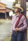 Handsome young man wearing cowboy hat standing thinking. Handsome young man wearing cowboy hat scott shirt and blue jean trousers standing thinking Royalty Free Stock Images