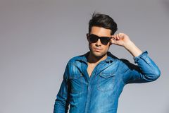 Handsome young man wearing a denim shirt holds his sunglasses Stock Photo