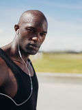 Handsome young man wearing earphones looking at camera. Image of handsome young man wearing earphones looking at camera. African male model outdoors Royalty Free Stock Photo
