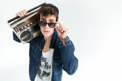 Handsome young man wearing glasses holding boombox. Picture of handsome young man wearing glasses standing  over white background and holding boombox. Looking at Stock Images