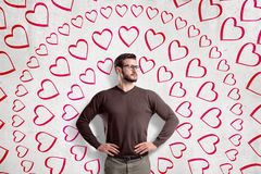 Handsome young man wearing glasses, standing with hands on waist, looking away, at wall with circular pattern of many. Hand-drawn hearts. St. Valentine`s stock images